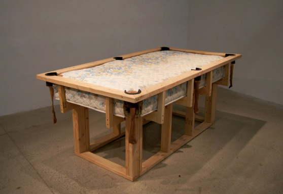 a sculpture composed to reference a pool table, made of pine studs and an old mattress.