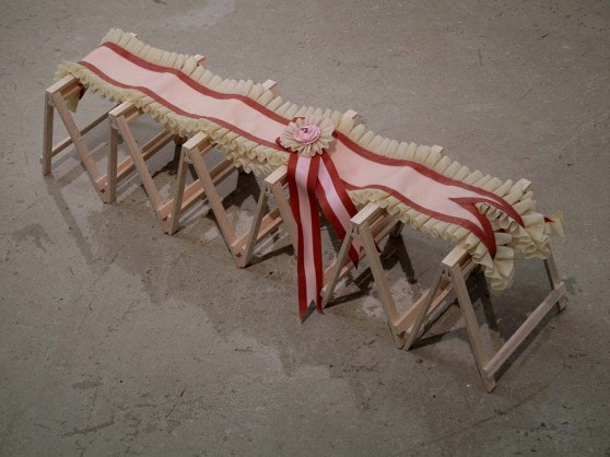 latex sash with tan ruffle, red and pink rosette and ribbons laid over the top of six miniature balsa wood sawhorses