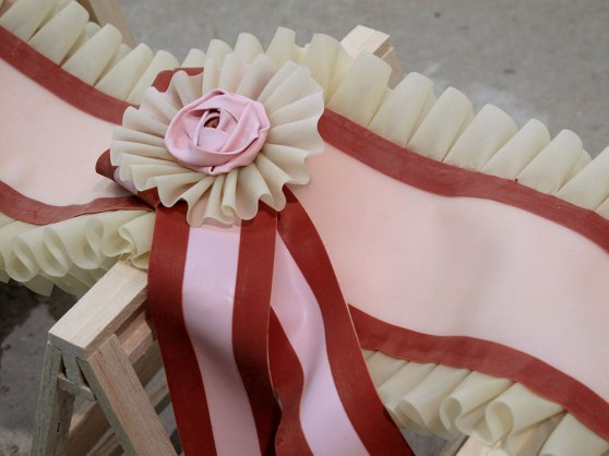 detail: latex red and pink rosette, ruffles and ribbons over the top of a miniature balsa wood sawhorse