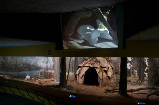 projection of figure in leather chaps sawing plaster saddle in half over a life-size diorama of a Native American settlement; the saddle from the projection is inserted into the diorama