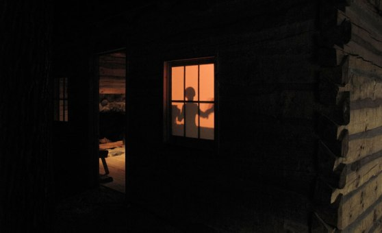 rear projection of figure into window in life-sized cabin in diorama