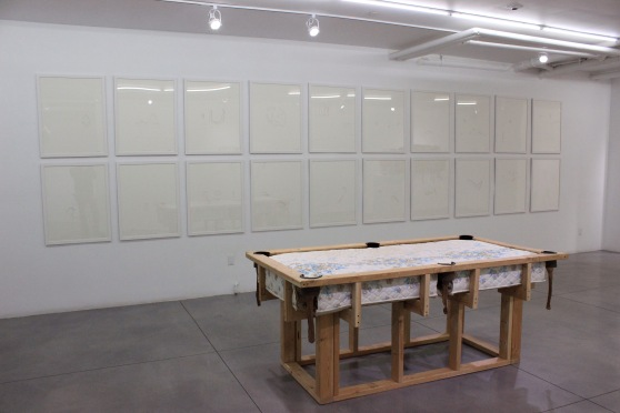"Foreground: ""A Pocket, A Cue, A Shot,"" a sculpture composed to reference a pool table, made of pine studs and an old mattress. Background: ""Ever Your Friend,"" a series of 20 framed laser cuts on white paper hung in a grid on the wall."
